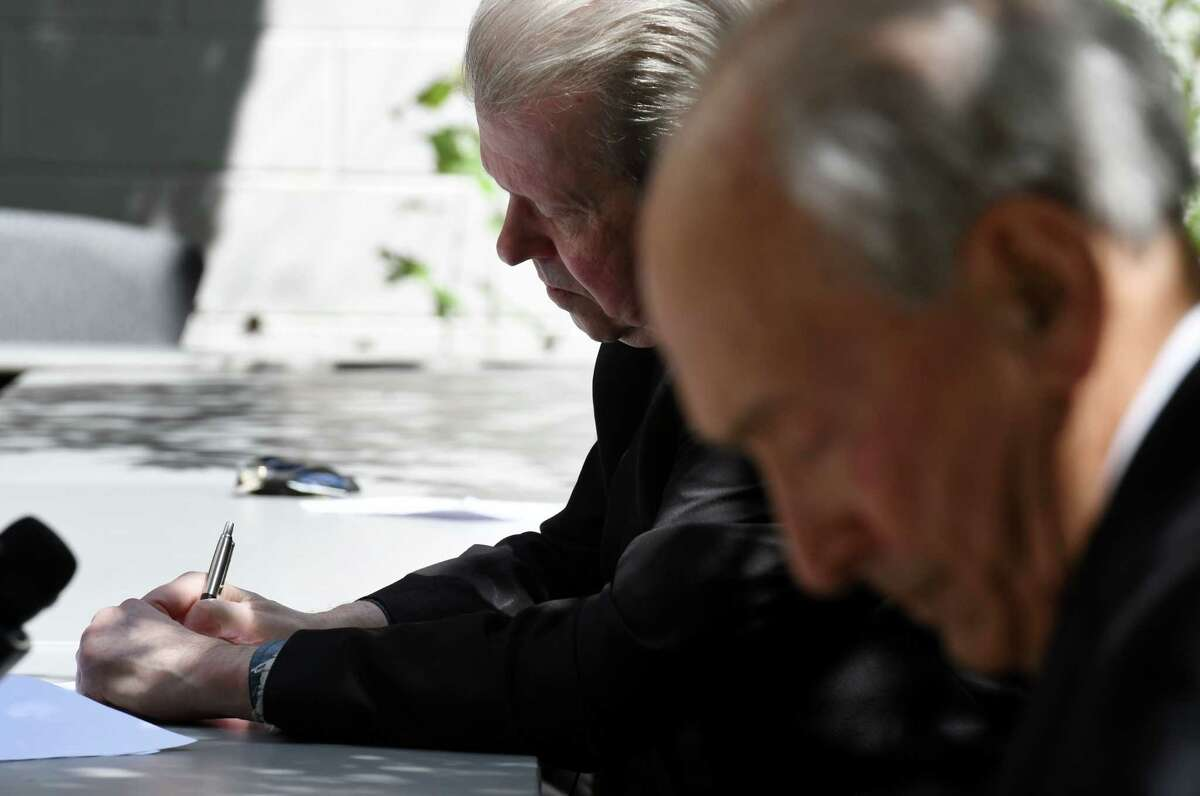 Bishop Edward Scharfenberger, left, signs over the deed to a two-acre parcel of property for the future Holocaust Memorial in Niskayuna to Dr. Michael Lozman, president of the Capital District Jewish Holocaust Memorial, right, during a ceremony on Thursday, Aug. 20, 2020, at the Roman Catholic Diocese of Albany Pastoral Center in Albany, N.Y. (Will Waldron/Times Union)