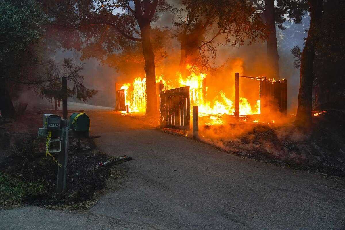 Th fence of a home is burned by the CZU August Lightning Complex Fire in Thursday, Aug. 20, 2020, near Bonny Doon, Calif.