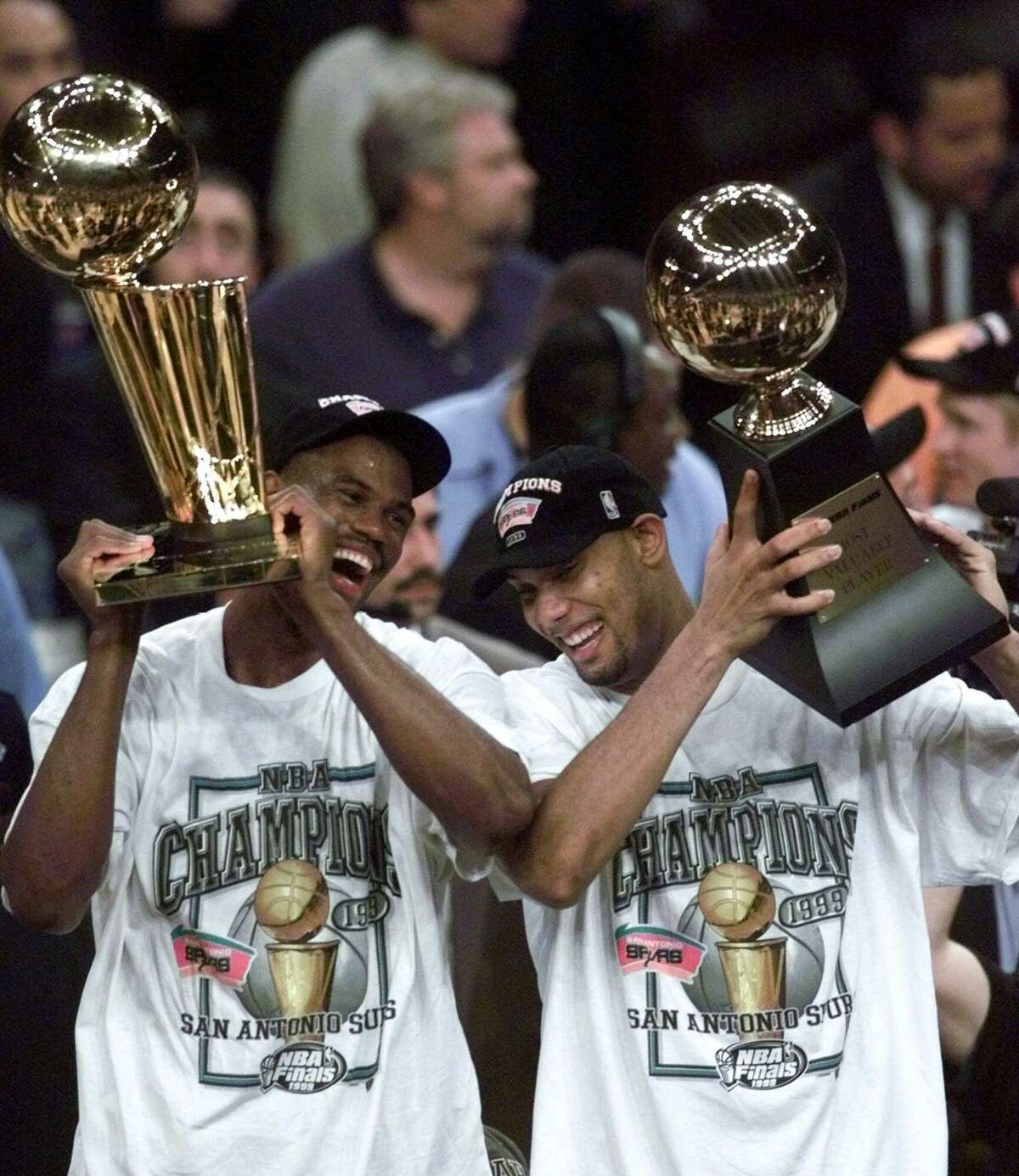 David Robinson, left, holds the NBA championship trophy as Tim Duncan holds the Most Valuable Player trophy after defeating the New York Knicks 78-77 in Game 5 of the 1999 NBA Finals. It was just the beginning of an incredible run.
