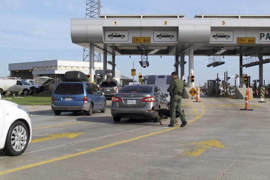 Inspectors and dogs walk around the cars at the Interstate 35 checkpoint near Laredo. Photo: Laredo Morning Times File