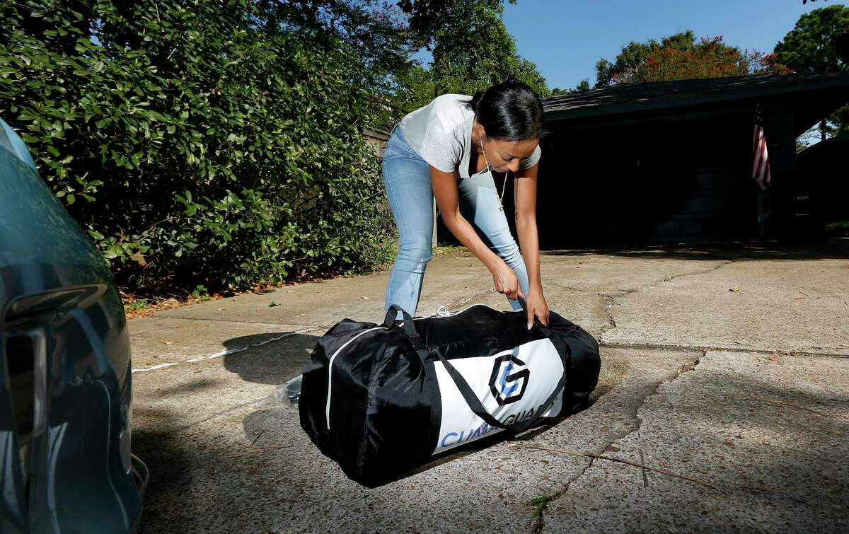 Climaguard CEO and founder Rahel Abraham demonstrates her product in Houston on Wednesday, Aug. 19, 2020. The chemical engineer is launching Climaguard, a heavy-duty plastic envelope for cars and furniture that protects them from flooding.