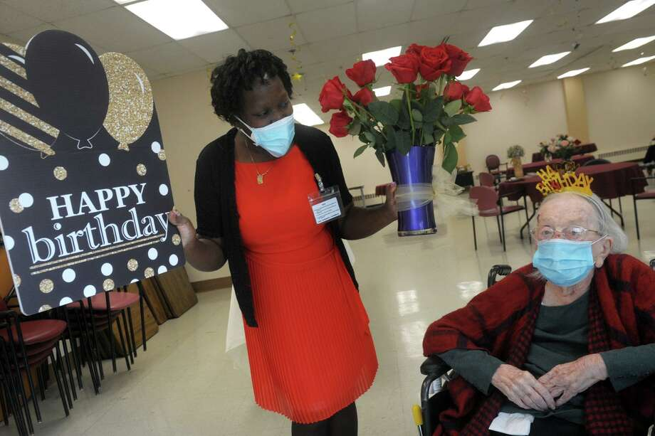 Operations director Zaida Stewart presents Lillian Grimmer with roses and a giant card prior to the party celebrating her 107th birthday at Hewitt Health and Rehab Center on Monday. Photo: Ned Gerard / Hearst Connecticut Media / Connecticut Post