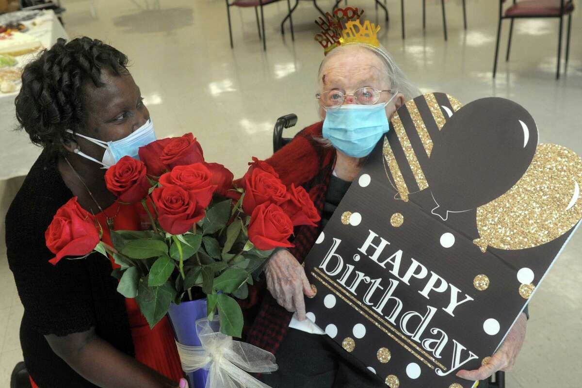 Operations director Zaida Stewart presents Lillian Grimmer with roses and a giant card prior to the party celebrating her107th birthday at Hewitt Health and Rehab Center, in Shelton, Conn. Aug. 17, 2020.