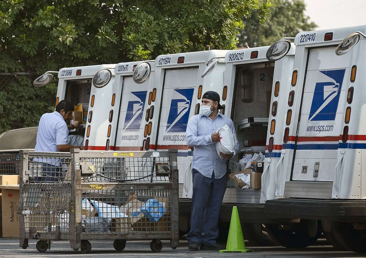 """Postal workers load packages in their mail delivery vehicles at the Panorama city post office on Thursday, Aug. 20, 2020 in the Panorama City section of Los Angeles. The Postmaster general announced Tuesday he is halting some operational changes to mail delivery that critics warned were causing widespread delays and could disrupt voting in the November election. Postmaster General Louis DeJoy said he would """"suspend"""" his initiatives until after the election """"to avoid even the appearance of impact on election mail."""" (AP Photo/Richard Vogel)"""
