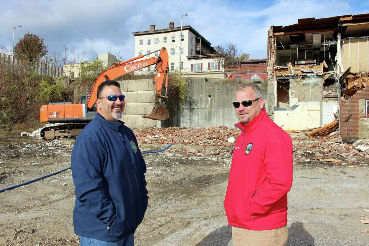 Derby Building Inspector Carlo Sarmiento, left, and Mayor Richard Dziekan watch the demolition of a building at 176 Main St. in Derby in 2018.