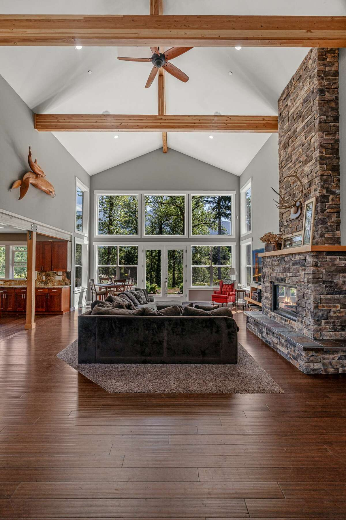 The cabin/castle/resort feel of the soaring ceiling and ornate stone hearth is enhanced by the wall of windows framing the sylvan setting.