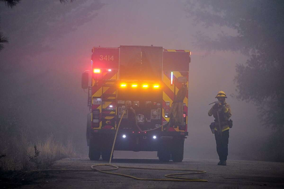 A firefighter walks along a smoke-filled road while fighting the CZU August Lightning Complex Fire on Thursday, Aug. 20, 2020, in Bonny Doon, Calif. (AP Photo/Marcio Jose Sanchez)