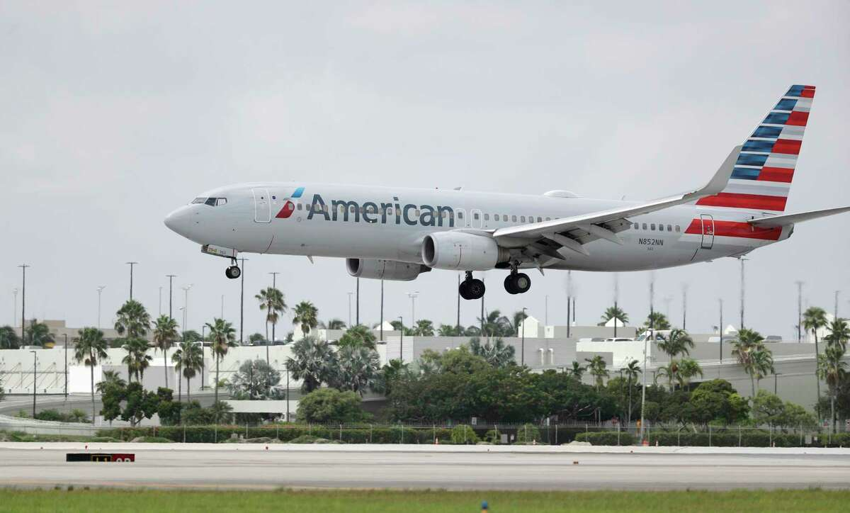 An American Airlines Boeing 737-823 lands at Miami International Airport, Monday, July 27, 2020, in Miami. American Airlines is dropping flights to 15 U.S. cities in October, when a federal requirement to serve those communities expires. American said Thursday, Aug. 20 that it will consider other changes unless the federal government provides more money to the embattled airline industry. (AP Photo/Wilfredo Lee)