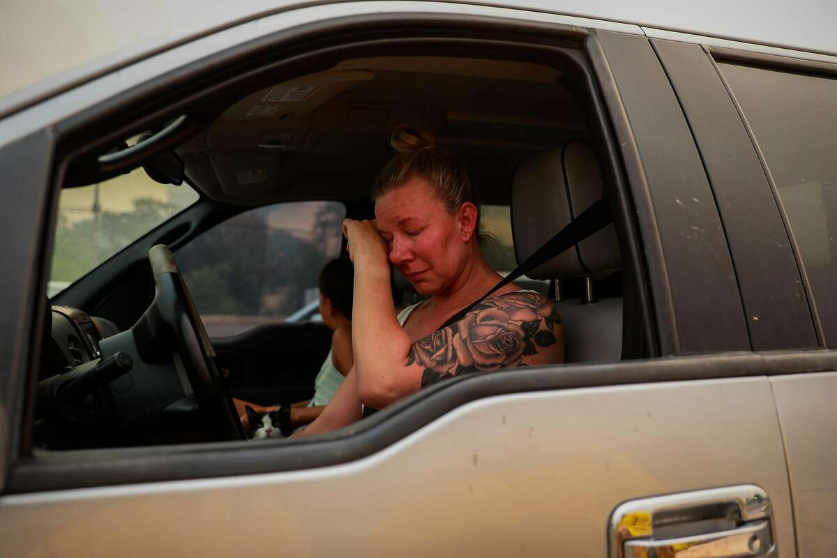 Gina Santos cries in her car after evacuating the LNU Lightning Complex Fire in Vacaville , Calif., on Wednesday, August 19, 2020. She moved to her �dream house� several months ago and was distraught that it might have burned down.