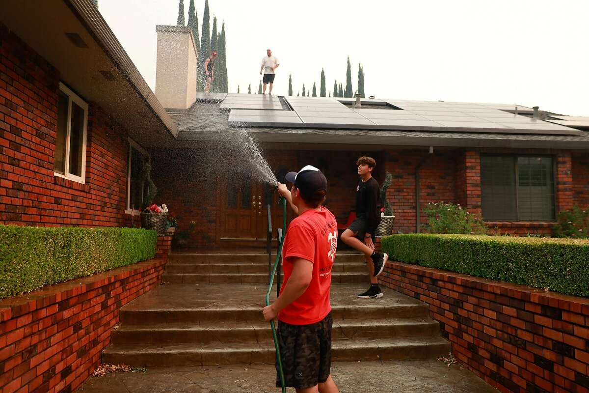 Jack Mitchell (center) waters down his grandfathers home as he tries to save it from impending fire with friends Tim Plowman (center, right) and Haedyn Gomes (right) before evacuating the LNU Lightning Complex Fire in Vacaville , Calif., on Wednesday, August 19, 2020.