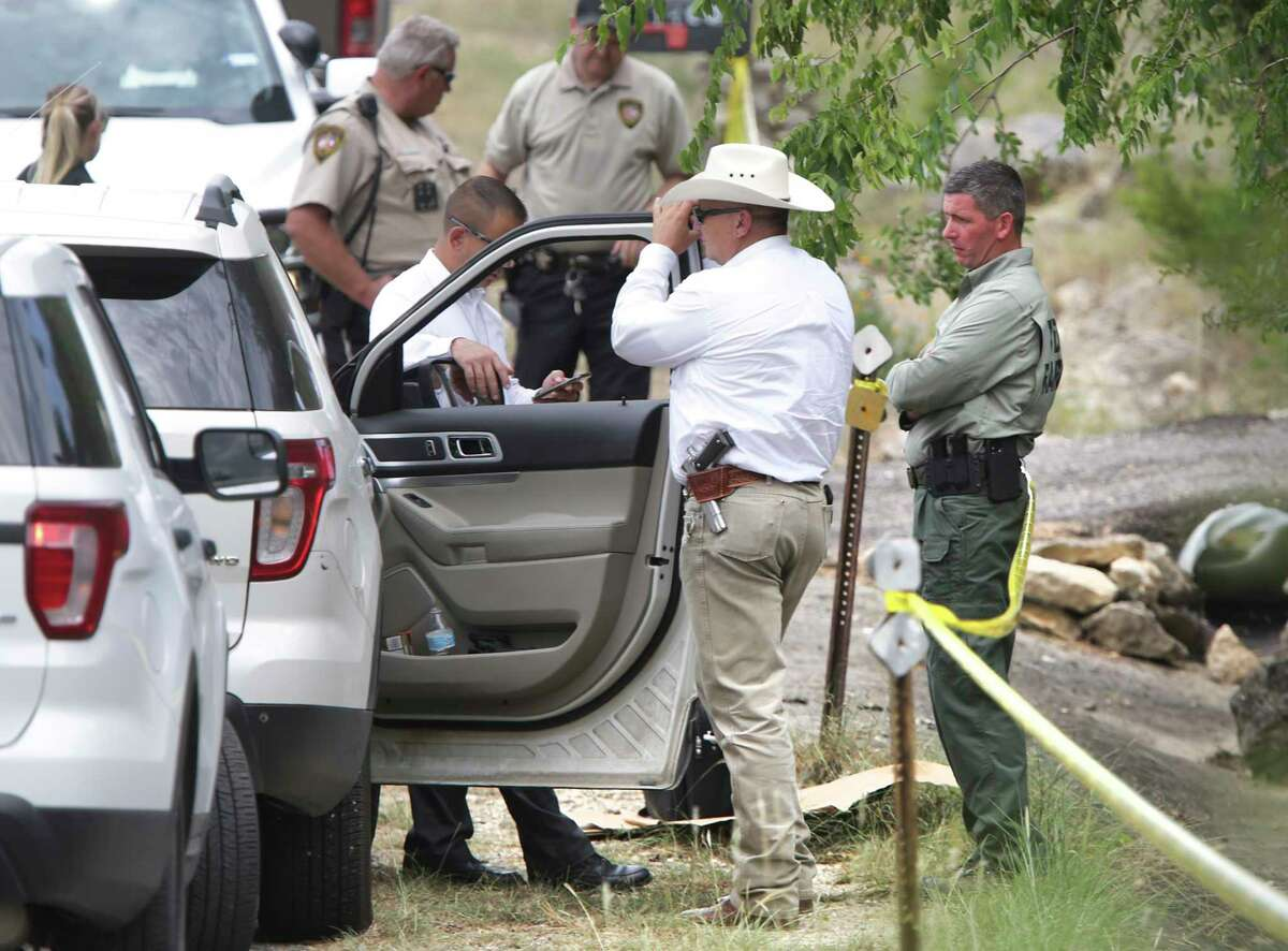 A Texas Ranger, right, talks with a Comal County Sheriff Deputies at the scene where another Sheriff Deputy was shot in the arm hile serving an arrest warrant, and airlifted to a hospital, on Thursday, Aug.20, 2020.