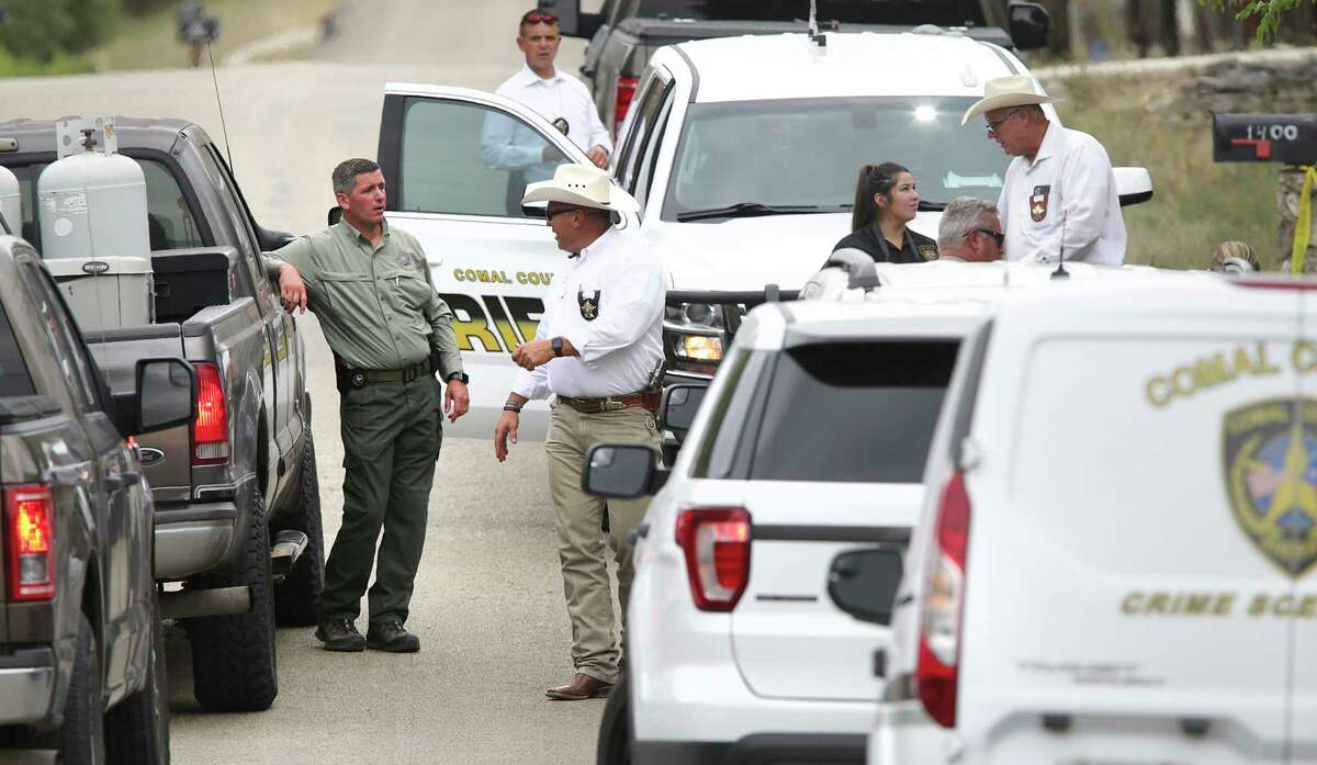 A Texas Ranger, left, talks with a Comal County Deputy Sheriff at the scene where another Sheriff Deputy was shot in the arm hile serving an arrest warrant, and airlifted to a hospital, on Thursday, Aug.20, 2020.