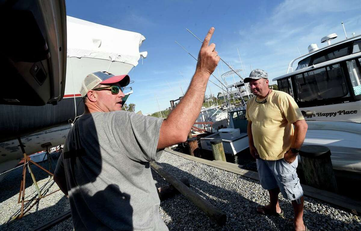 Kevin Barosso, left, of Westbrook and Chris Hales of Waterbury talk about the yacht Lady May at Harry's Marina in Westbrook Aug. 20, 2020. President Donald Trump's former campaign strategist, Steve Bannon, was arrested on federal charges earlier in the day from that yacht off the coast of Westbrook.