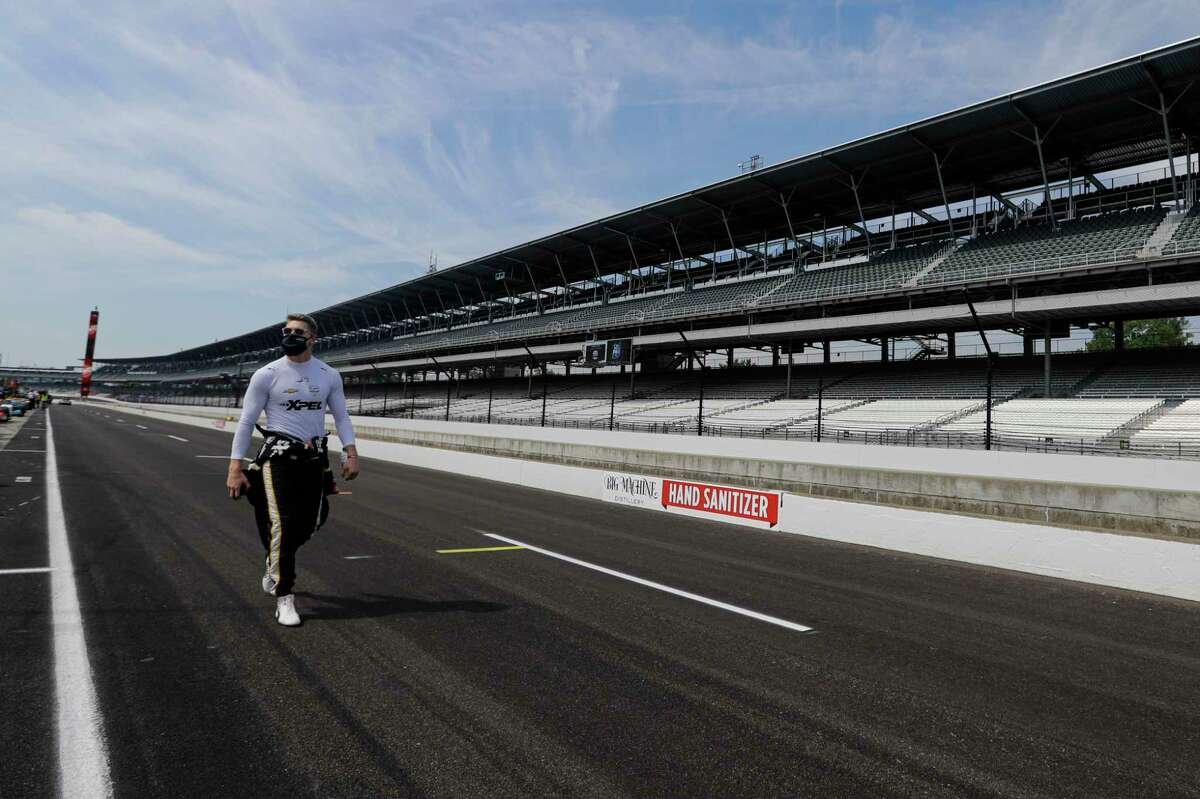 FILE - In this July 30, 2020, file photo, race driver Josef Newgarden walks through the pit area before the start of practice for an IndyCar auto race at Indianapolis Motor Speedway in Indianapolis. There was always going to be an Indianapolis 500 this year, be it with full fans, limited fans or, where Indianapolis Motor Speedway finally landed, with no fans at all. Roger Penske has been determined for this staple of American sporting events to go on and the track will open Wednesday, Aug. 12 for activity. (AP Photo/Darron Cummings)