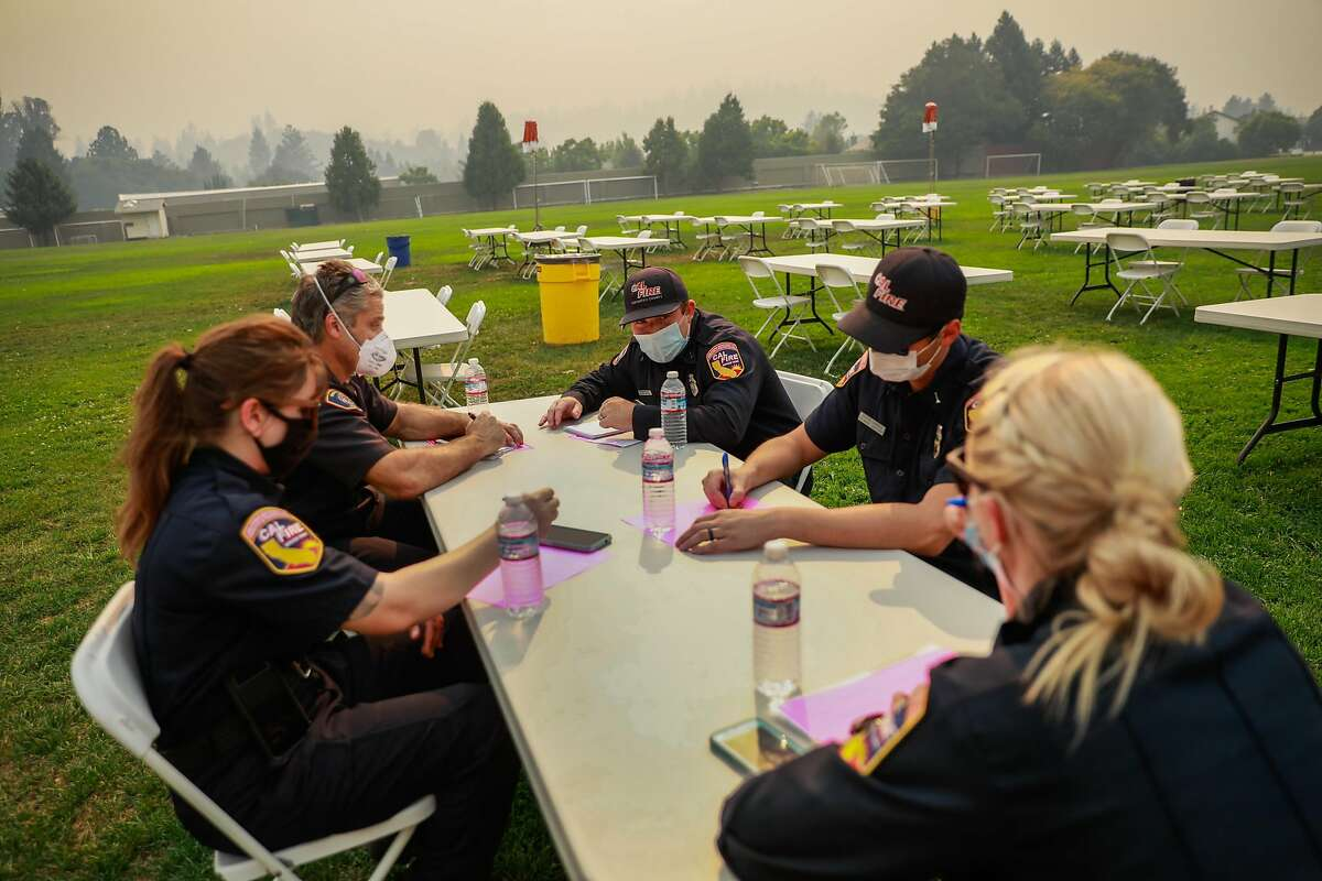Base camp managers discuss strategy at a nearly empty incident command center during the CZU Lightning Complex Fire on Thursday, Aug. 20, 2020 in Scotts Valley, California.