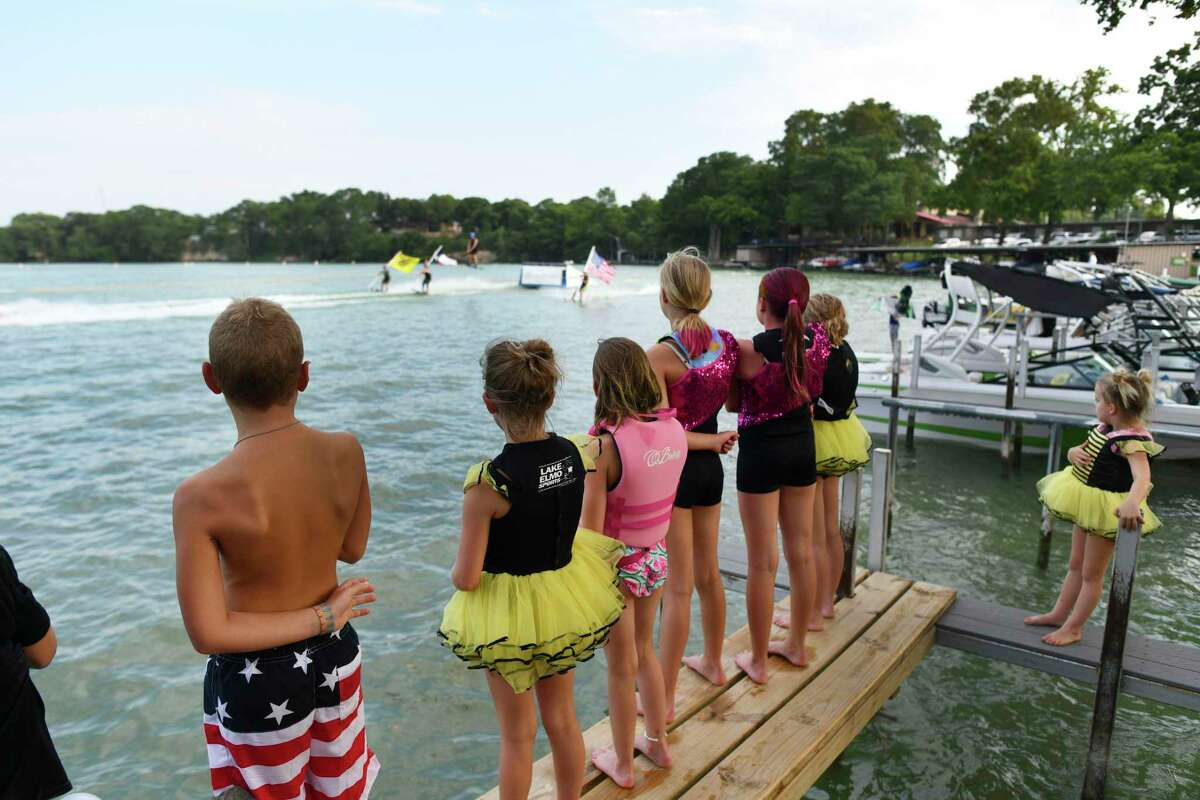 Members of the Ski Bees watch a ski jumper and a skier holding the American flag before a ski show on Lake McQueeney. A judge ruled Thursday that a lawsuit filed by 278 property owners against the Guadalupe-Blanco River Authority regarding its deteriorating dams may proceed on some of its claims.