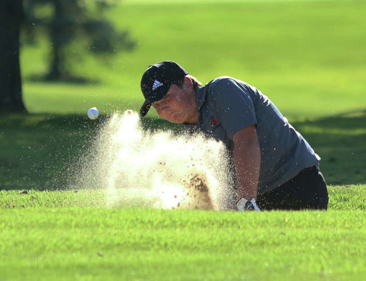 Alton's Alec Schmieder hits from the bunker on hole No. 8 at Belk Park golf course Thursday afternoon at the Madison County Tournament in Wood River.