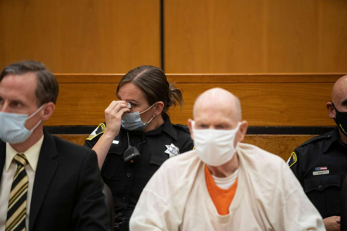 A Sacramento County Sheriff's deputy wipes her eye as she listens in to the third day of victim impact statements and guards Joseph James DeAngelo (right) at the Gordon D. Schaber Sacramento County Courthouse on Thursday, Aug. 20, 2020, in Sacramento, Calif. DeAngelo, 74, admitted being the infamous Golden State Killer. He will be formally sentenced to life in prison on Friday under a plea agreement that allows DeAngelo to avoid the death sentence. The former police officer in California eluded capture for four decades. He has admitted 13 murders and nearly 50 rapes between 1975 and 1986.