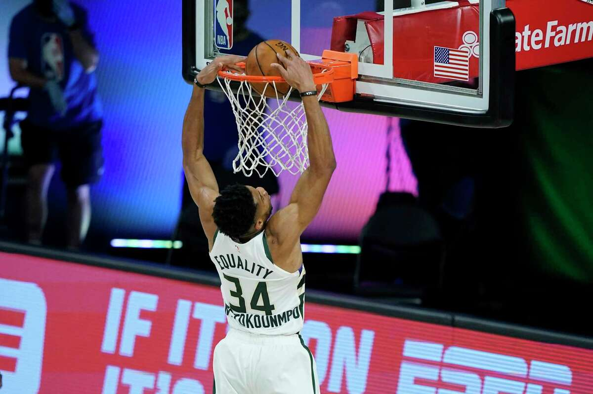 LAKE BUENA VISTA, FLORIDA - AUGUST 20: Giannis Antetokounmpo #34 of the Milwaukee Bucks scores against the Orlando Magic during the first half of an NBA basketball first round playoff game on August 20, 2020 in Lake Buena Vista, Florida. NOTE TO USER: User expressly acknowledges and agrees that, by downloading and or using this photograph, User is consenting to the terms and conditions of the Getty Images License Agreement. (Photo by Ashley Landis - Pool/Getty Images)