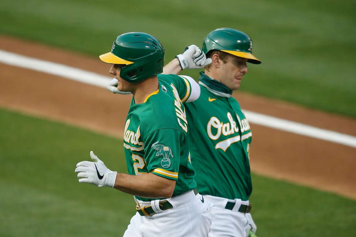 OAKLAND, CALIFORNIA - AUGUST 20: Matt Chapman #26 of the Oakland Athletics celebrates with Mark Canha #20 after hitting a solo home run in the bottom of the first inning against the Arizona Diamondbacks at RingCentral Coliseum on August 20, 2020 in Oakland, California. (Photo by Lachlan Cunningham/Getty Images)