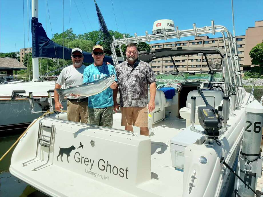 Evart's Mark Sochocki (center) and his Grey Ghost partners show some king salmon from the Ludington tournament and the trophy for the biggest steelhead in a Manistee tournament earlier in the summer. (Courtesy photo)