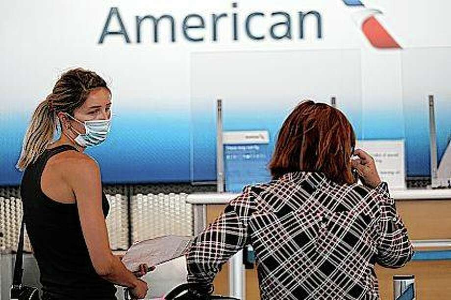 Travelers wear mask June 16 as they wait at the American Airlines ticket counter in Terminal 3 at O'Hare International Airport in Chicago. American Airlines has said it is cutting service to 15 cities nationwide. including Springfield. Photo: Nam Y. Huh | Associated Press
