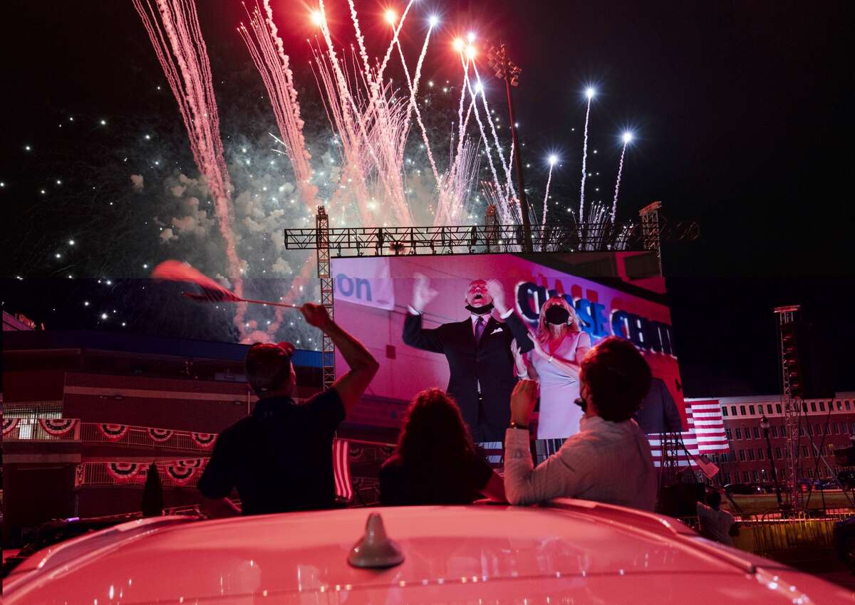 Supportes cheer from their cars as Democratic presidential candidate former Vice President Joe Biden and his wife Jill Biden are seen on a huge monitor as fireworks light up the nigh sky on the fourth day of the Democratic National Convention, Thursday, Aug. 20, 2020, outside of the Chase Center in Wilmington, Del. (AP Photo/Carolyn Kaster)