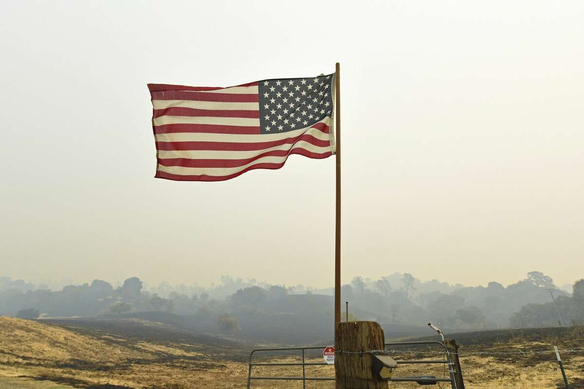 A U.S. flag on Cantelow Road waves in the wind after surviving a fire in Vacaville, Calif., on Thursday, Aug. 20, 2020. The LNU Lightning Complex fires began in Napa and Sonoma counties and traveled into Solano, Lake and Yolo counties while burning more than 200 square miles.
