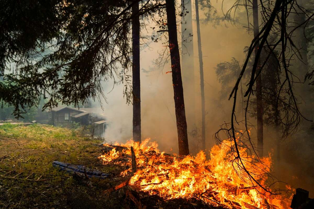 A fire burns near a structure along Pine Flat road during the CZU August Lightning Complex Fires on Thursday, Aug. 20, 2020 in Felton, CA.