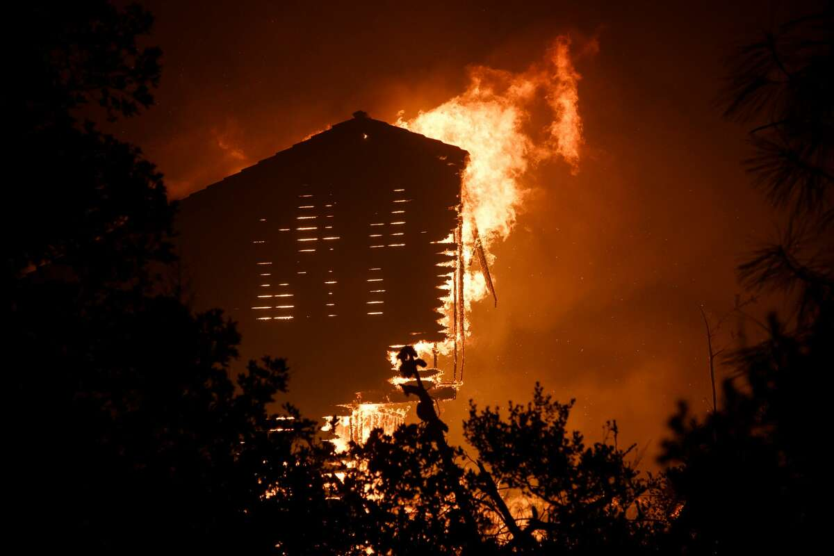 A structure burns in a residential neighborhood near Empire Grade in Bonny Doon, Calif., in the early Thursday morning on Aug. 20, 2020.