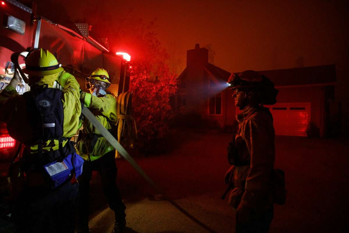 As the CZU August Lightning Complex fire burns houses near by, Santa Cruz County Central Fire Protection District firefighters work in a residential neighborhood near Empire Grade to protect the remaining homes in Bonny Doon, Calif., in the early morning of Aug. 20, 2020.
