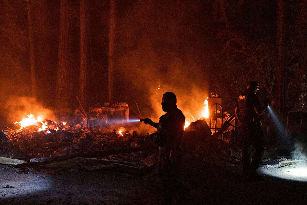 An officer from Watsonville Police Department looks at a home along Highway 236 near Boulder Creek that was destroyed in the CZU Lightning Complex Fire on Aug. 20, 2020.