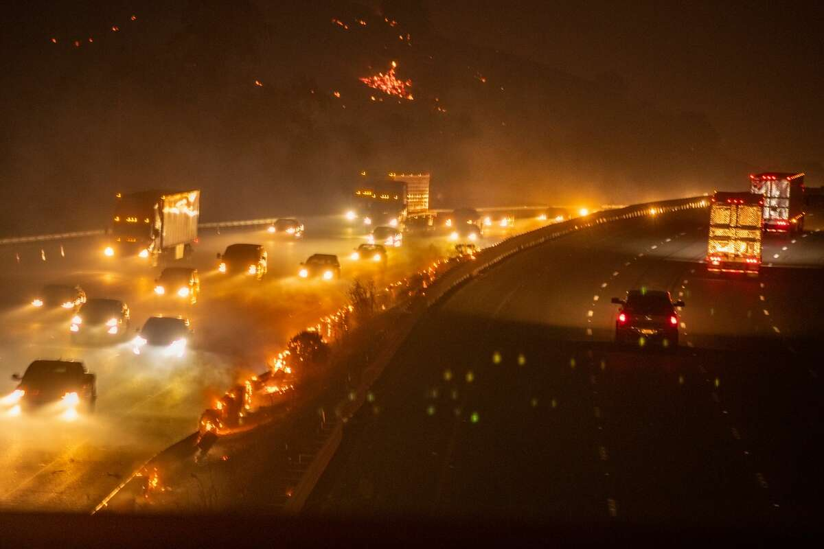 Traffic begins to move in both directions as hot spots continue burning guardrails after the LNU Lightning Complex fire jumped on I-80 freeway forcing to shut it down in Fairfield, Calif., on Wednesday, Aug., 19, 2020.