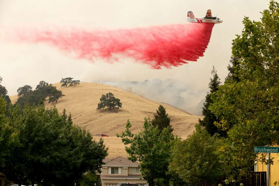 A Cal Fire tanker drops fire retardant on a hillside behind homes in the Rolling Hills neighborhood of Fairfield, Calif., on Wednesday, Aug. 19, 2020. Residents were ordered to evacuate as the LNU Lightning Complex wildfire threatened the neighborhood. Photo: MediaNews Group/East Bay Times Via Getty Images/MediaNews Group Via Getty Images / Bay Area News Group