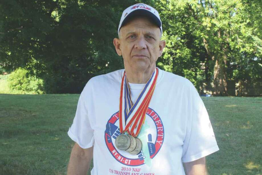 Pete Kenyon wears some of the clothing he has receieved during his years competing in the transplant games. Photo: Ben Holbrook, Contributed Photo / Darien News