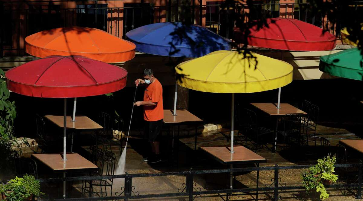 A worker wearing a mask to protect against the spread of COVID-19 power washes an exterior dinning area along the River Walk, Wednesday, Aug. 12, 2020, in San Antonio. (AP Photo/Eric Gay)