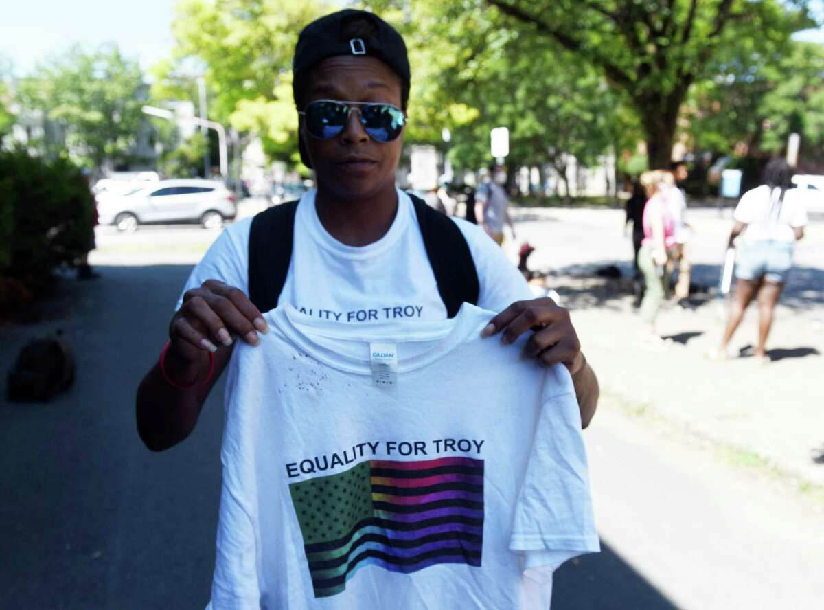 Tasheca Medina, of Equality for Troy, holds a blood-stained shirt worn by activist Ken Zeoli, who said he was injured at Troy police headquarters after being taken into custody following his effort to file a complaint on Friday, Aug. 21, 2020, in Troy, N.Y. Supporters said Zeoli, of the Coalition for Barker Park, was being evaluated for a broken collarbone. Troy police are calling the assault claim