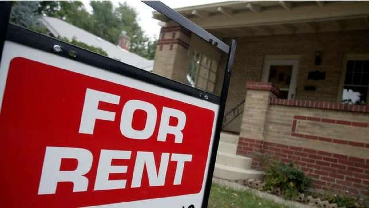 FILE - a for rent sign stands in front of a home