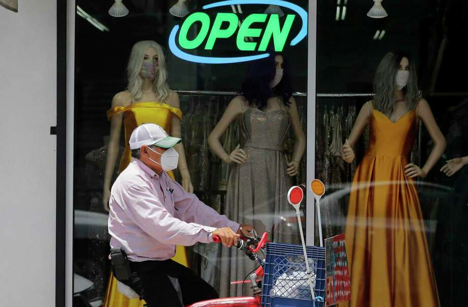 FILE - In this July 30, 2020, file photo, a cyclist passes a display window with mask covered mannequins at a dress store in McAllen, Texas. The number of laid-off workers applying for unemployment aid fell below 1 million last week for the first time since the pandemic intensified five months ago, yet still remains at a high level. (AP Photo/Eric Gay, File) Photo: Eric Gay, STF / Associated Press / Copyright 2020 The Associated Press. All rights reserved.