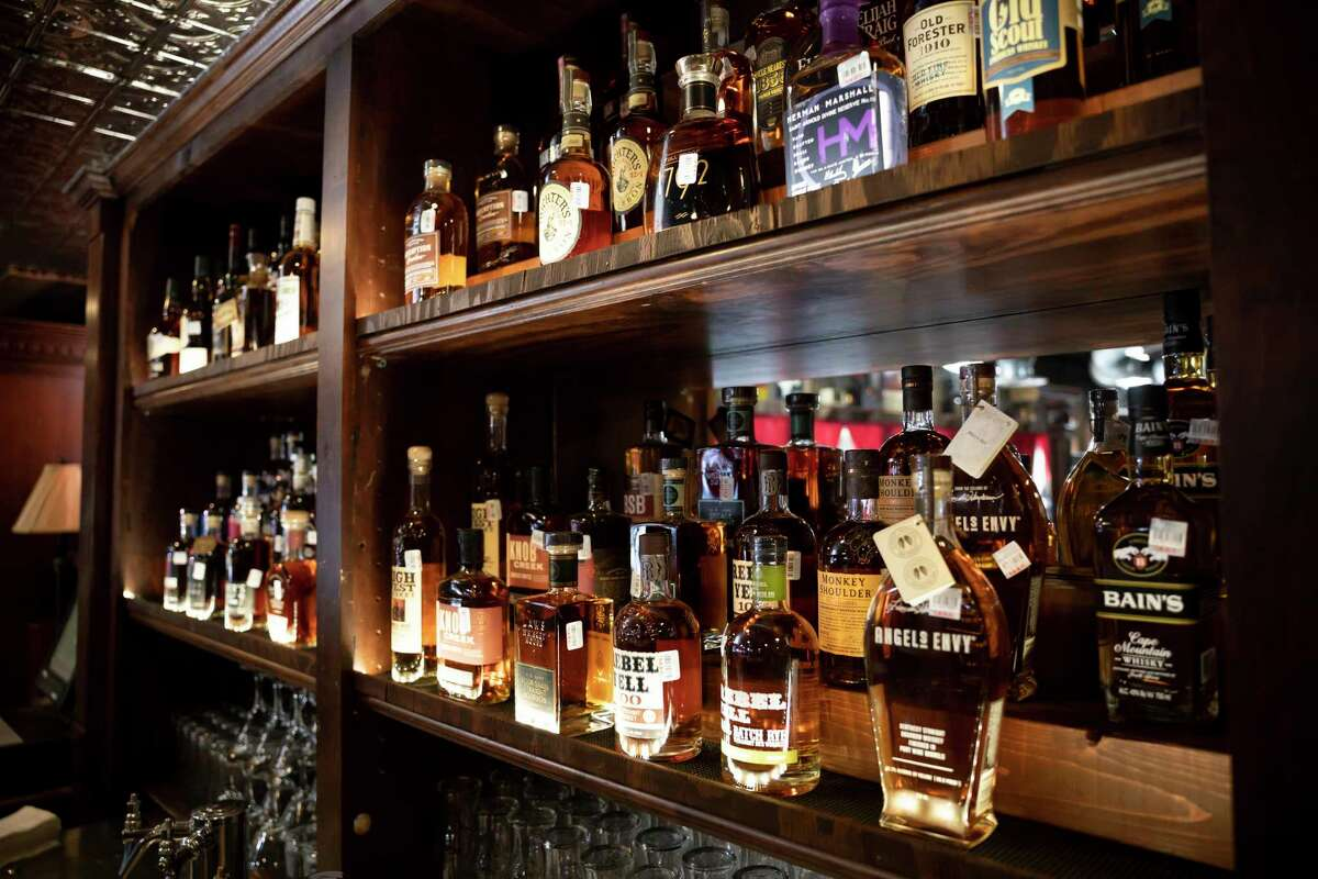 Bottles of whiskey are displayed on a cabinet at Dosey Doe BBQ restaurant, Thursday, Aug. 20, 2020, in The Woodlands. The new bar will feature over 150 whiskies from around the world and will open Sept. 1.