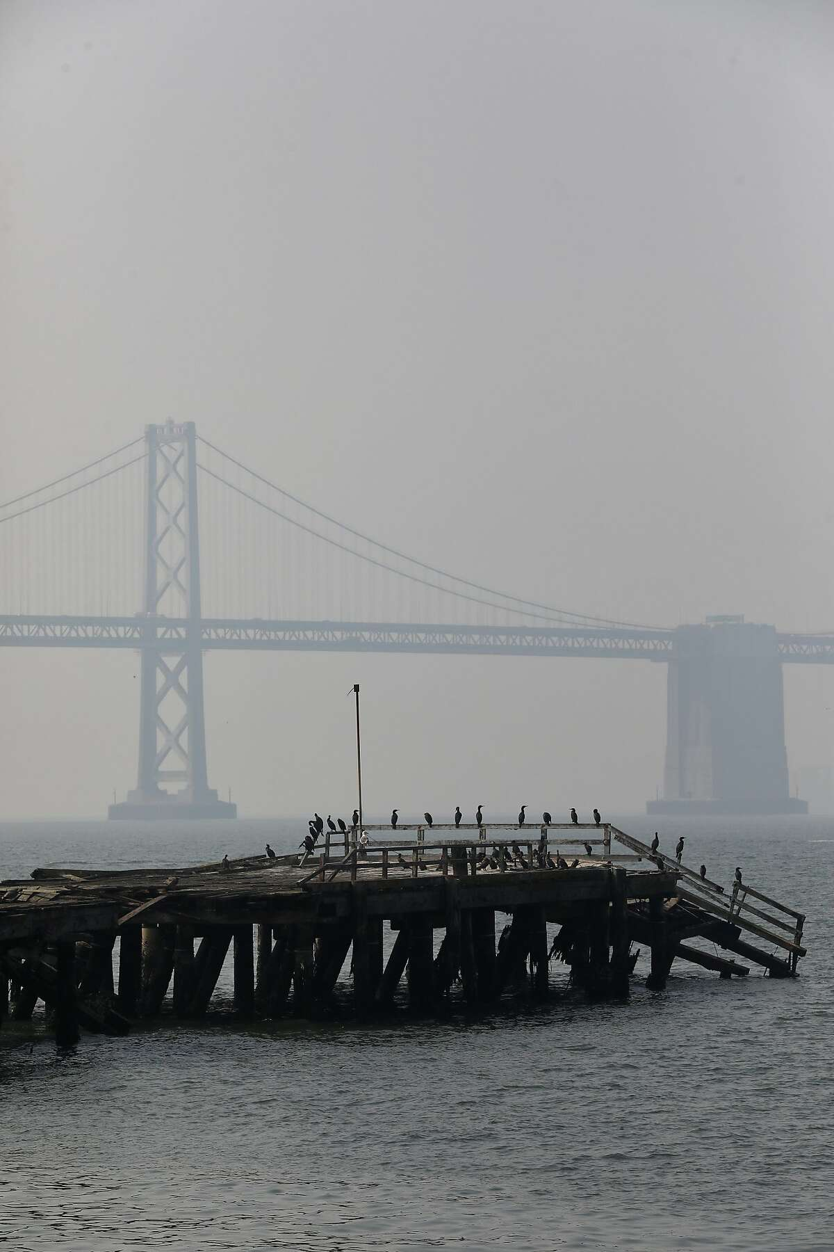 A smoky haze from multiple wildfires in the Bay Area continues to cover the Bay Bridge as seen from Treasure Island, Calif., on Friday, August 21, 2020.