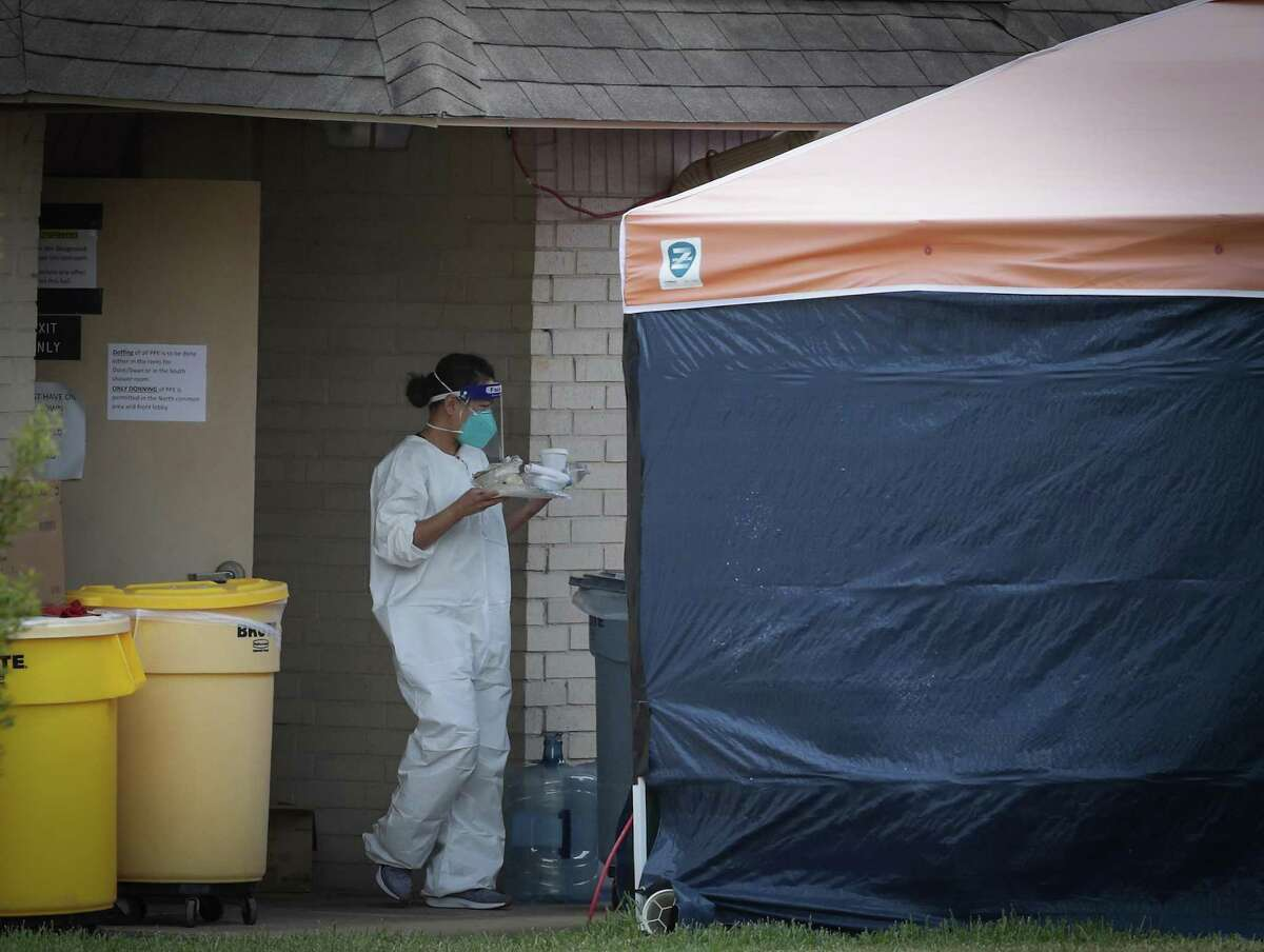 A person in PPE equipment exits Windsong Care Center on Thursday, July 16, 2020, in Pearland.