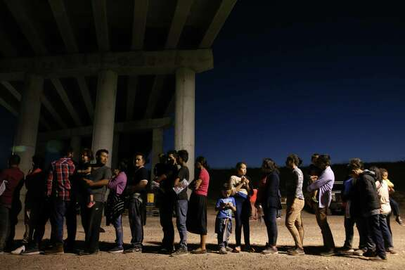 NOT FOR PUBLICATION US Border Patrol agents gather information on a large group of mostly Central American migrants that turned themselves into the agents by the Anzalduas International Bridge in Hidalgo County, Texas, Thursday, July 18, 2019.