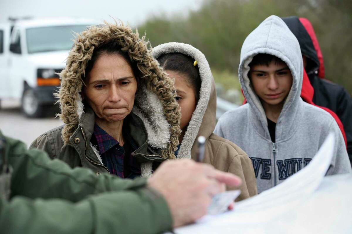 Lorena Arevalo, 43, center, from El Salvador, and her five children turn themselves in to U.S. Border Patrol agents by Anzalduas Park in Hidalgo County, Texas, Wednesday, Jan. 30, 2019. A group of 39 immigrant families seeking asylum turned themselves in to U.S. Border patrol agents after crossing the Rio Grande illegally. On Tuesday, a group of 99 immigrants was picked up in the area.