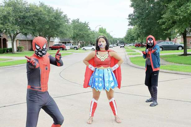 Isaiah Torres, Jasmine Saenz and Stephan Torres dress as superheroes to cheer up kids around Pearland during the coronavirus pandemic.