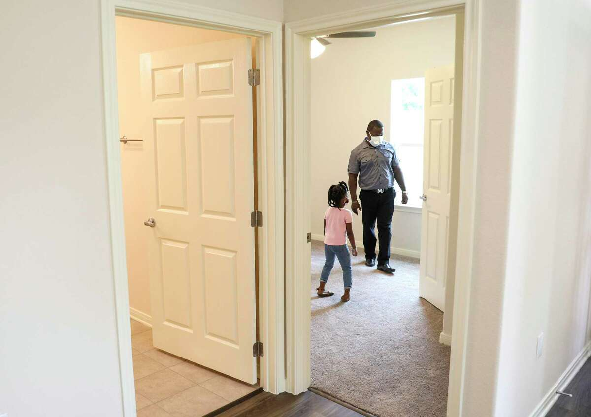 Lloyd Nelms and his niece Bailee, 4, look through their newly rebuilt home Friday, May 29, 2020, in Houston. Nelms said he contacted the GLO after the city of Houston failed to repair his home after it was flooded during Hurricane Harvey.