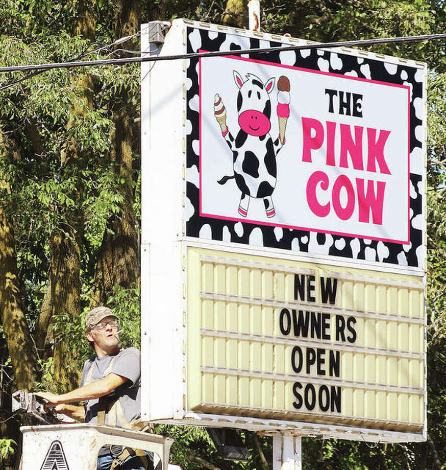 An employee of Arrow Outdoor Signs and Advertising moves in to finish the job of changing signs on the former Ketchum's Corner Kreem at the corner of Alby and Elm streets Thursday. The ice cream business has new owners who have repainted the shop and renamed it The Pink Cow.