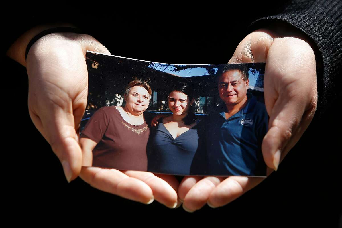 Kristin Urquiza, holds a photo of herself (center) with her father Mark Urquiza (right) and mother Brenda Urquiza (left) as she stands for a portrait on Thursday, August 20, 2020 in San Francisco, Calif. Kristin Urquiza, a San Francisco environmentalist, gave a speech at the Democratic National Convention about her dad's death from COVID-19.
