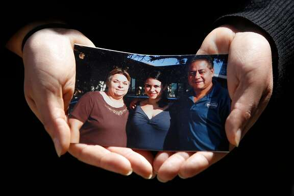 """Kristin Urquiza, holds a photo of herself (center) with her father Mark Urquiza (right) and mother Brenda Urquiza (left) as she stands for a portrait on Thursday, August 20, 2020 in San Francisco, Calif.  Kristin Urquiza, a San Francisco environmentalist, gave a speech at the Democratic National Convention about her dad's death from COVID-19. """"His only pre-existing condition was supporting Donald Trump,"""" she said."""