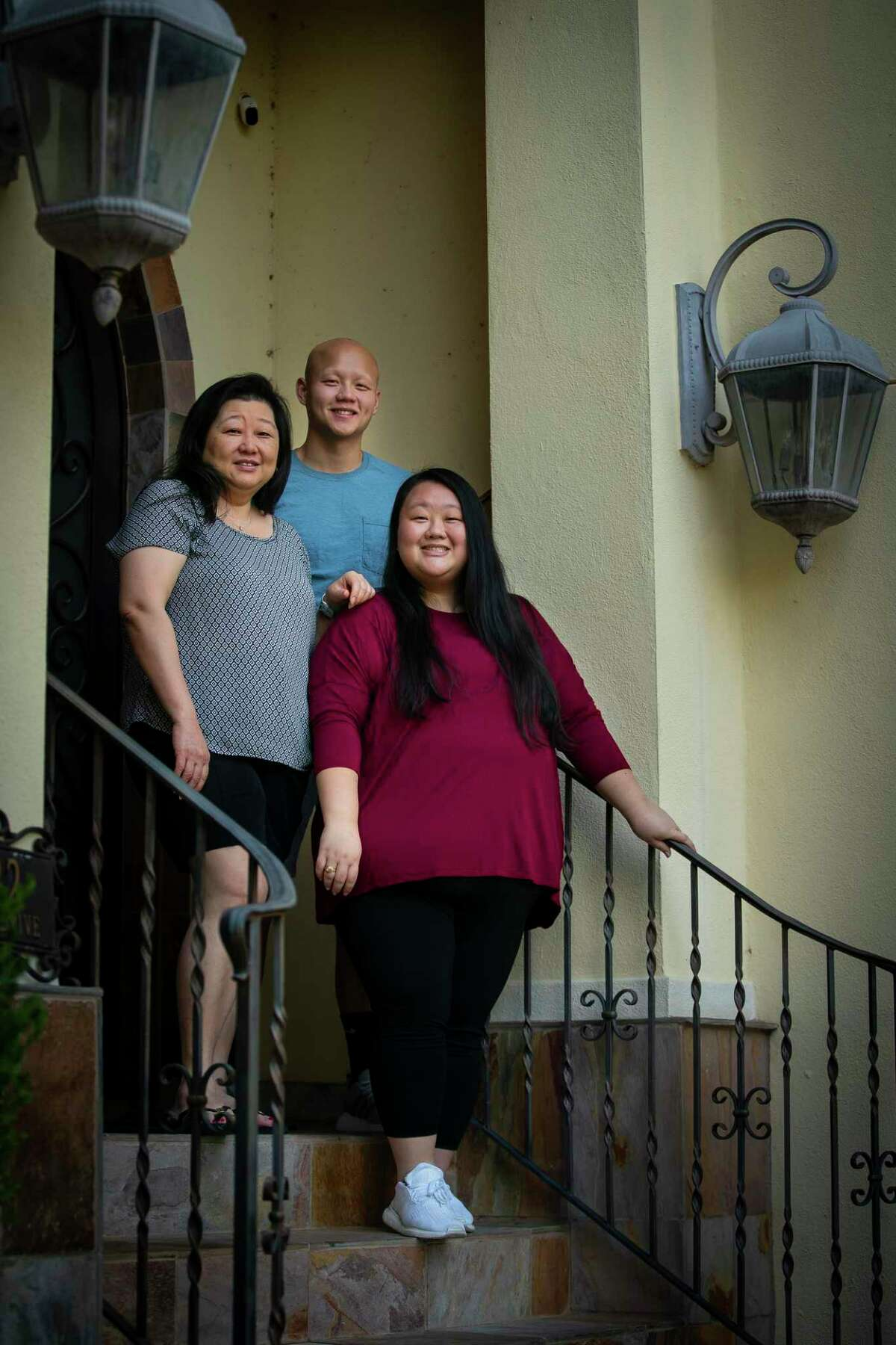Ashlee Phan, photographed with her mother, Margaret Lynn, and brother Nick Phan, was working her job as a surgical nurse when she began running a fever. At only 25 years-old, she did not think it was COVID-19. Days later, her mom found her unconscious and near death. Ashlee, who is now negative, spent time in the ICU and has since been recovering at her mother's home. Photographed on Thursday, Aug. 13, 2020, in Houston.
